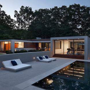 Idee per una grande piscina a sfioro infinito minimalista rettangolare dietro casa con lastre di cemento