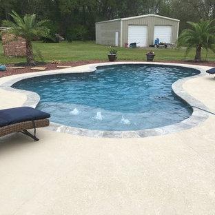 Esempio di una piccola piscina naturale minimal personalizzata dietro casa con fontane e pedane