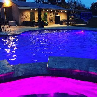 Immagine di una grande piscina naturale personalizzata dietro casa con una vasca idromassaggio e pedane