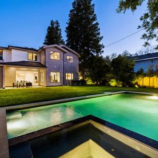 Foto de piscina con fuente campestre, grande, en forma de L, en patio trasero