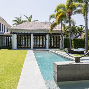 Foto di una grande piscina monocorsia tropicale rettangolare dietro casa con fontane e pavimentazioni in cemento
