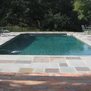 Imagen de piscina natural, clásica, de tamaño medio, rectangular, en patio trasero, con adoquines de piedra natural