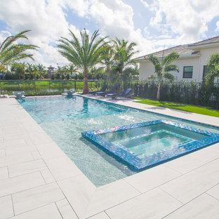 Example of a large minimalist backyard rectangular infinity hot tub design in Miami