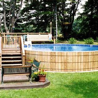 Ejemplo de piscina elevada, tradicional, redondeada, en patio trasero, con losas de hormigón