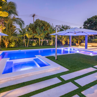 Design ideas for a large modern backyard custom-shaped lap pool in Miami with a hot tub.