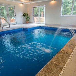 Foto de piscina con fuente alargada, actual, extra grande, interior y rectangular, con suelo de baldosas