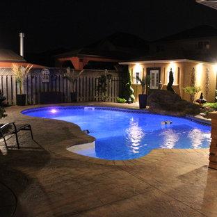 Ejemplo de piscina con fuente alargada, exótica, de tamaño medio, tipo riñón, en patio trasero, con losas de hormigón