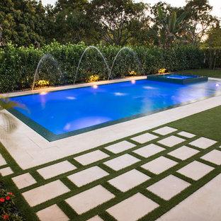 Imagen de piscina con fuente alargada, actual, grande, rectangular, en patio trasero
