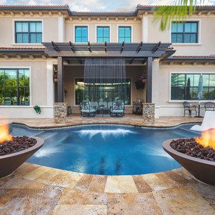 Inredning av en amerikansk stor anpassad pool på baksidan av huset, med en fontän och naturstensplattor
