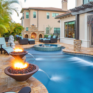 Photo of a large mediterranean backyard custom-shaped pool in Miami with a water feature and natural stone pavers.