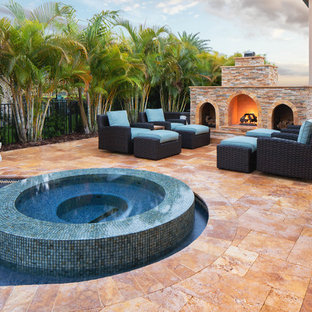Large arts and crafts backyard custom-shaped pool in Miami with a water feature and natural stone pavers.
