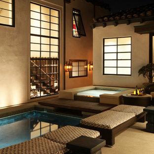 Esempio di una grande piscina monocorsia minimal rettangolare in cortile con una vasca idromassaggio e lastre di cemento