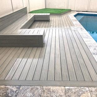 Immagine di una piscina minimalista di medie dimensioni e dietro casa con pedane