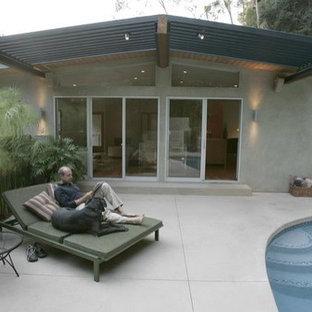 Modelo de piscina contemporánea, de tamaño medio, tipo riñón, en patio lateral, con losas de hormigón