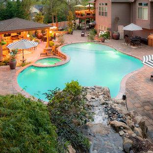 Imagen de piscina mediterránea, grande, tipo riñón, en patio trasero, con adoquines de ladrillo