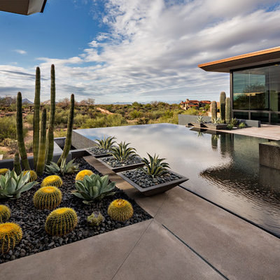 Inspiration for a large southwestern backyard concrete and rectangular infinity hot tub remodel in Phoenix