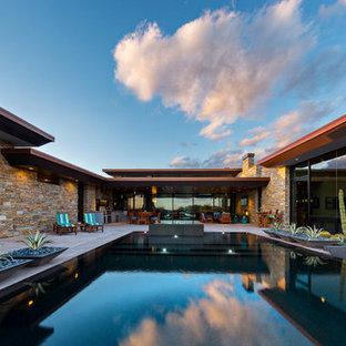 Ejemplo de piscinas y jacuzzis infinitos, de estilo americano, grandes, rectangulares, en patio trasero, con losas de hormigón
