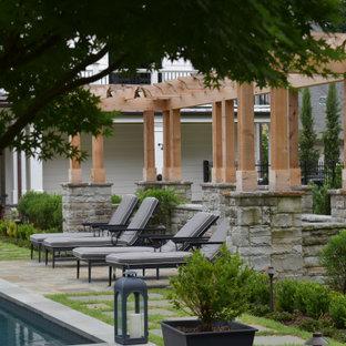 Imagen de piscina alargada, tradicional, grande, rectangular, en patio trasero, con adoquines de piedra natural