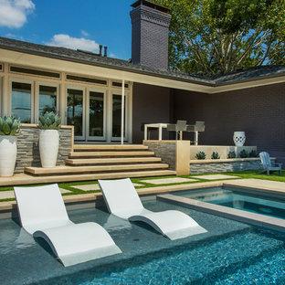 Bild på en mellanstor funkis rektangulär pool på baksidan av huset, med spabad
