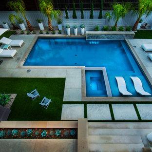 Immagine di una piscina minimalista rettangolare di medie dimensioni e dietro casa con una vasca idromassaggio