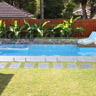 Foto de piscinas y jacuzzis alargados, tropicales, de tamaño medio, rectangulares, en patio trasero, con adoquines de piedra natural