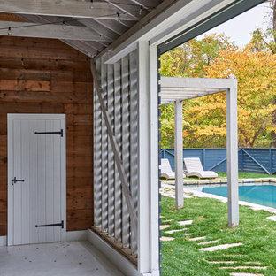 Imagen de casa de la piscina y piscina natural, campestre, de tamaño medio, rectangular, en patio trasero, con adoquines de piedra natural