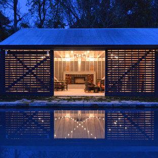 Imagen de casa de la piscina y piscina natural, de estilo de casa de campo, de tamaño medio, rectangular, en patio trasero, con adoquines de piedra natural