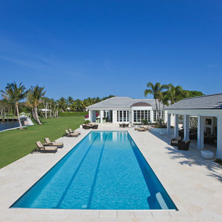 Huge trendy backyard tile and rectangular lap pool house photo in Miami