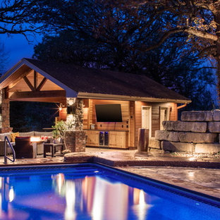 Pool house - mid-sized craftsman backyard stone and rectangular pool house idea in Omaha