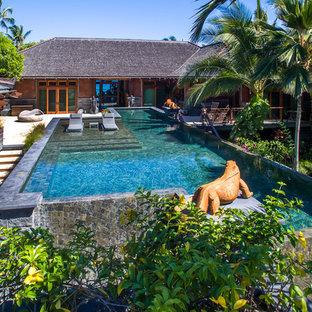 Ejemplo de piscina infinita, tropical, a medida, en patio trasero