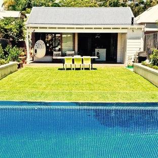 Imagen de piscina elevada, actual, rectangular, en patio trasero, con entablado