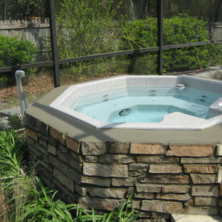 Example of a small trendy backyard stone and custom-shaped aboveground hot tub design in Tampa