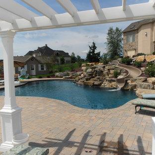 Foto de piscina con tobogán natural, tradicional, a medida, en patio trasero, con adoquines de ladrillo