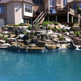 Modelo de piscina con tobogán natural, tradicional, a medida, en patio trasero, con adoquines de ladrillo