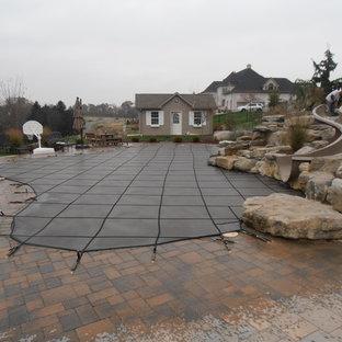 Diseño de piscina con tobogán natural, clásica, a medida, en patio trasero, con adoquines de ladrillo