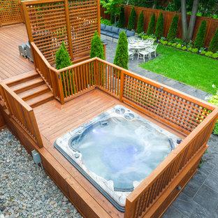 Réalisation d'une grand piscine sur une terrasse en bois hors-sol et arrière bohème rectangle avec un bain bouillonnant.