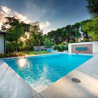 Esempio di una grande piscina moderna rettangolare dietro casa con pedane