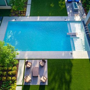 Esempio di una grande piscina minimalista rettangolare dietro casa con pedane