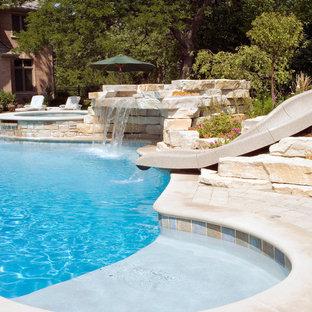 Неиссякаемый источник вдохновения для домашнего уюта: огромный естественный бассейн произвольной формы на заднем дворе в стиле рустика с водной горкой и мощением тротуарной плиткой