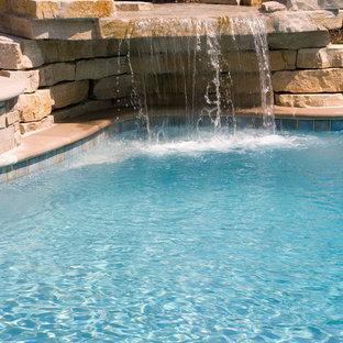 Свежая идея для дизайна: огромный естественный бассейн произвольной формы на заднем дворе в стиле рустика с водной горкой и мощением тротуарной плиткой - отличное фото интерьера