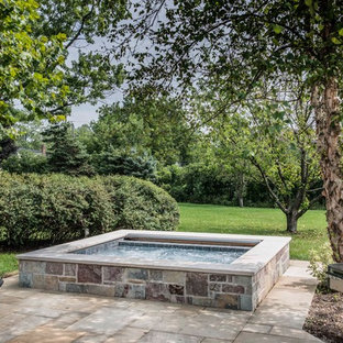 This is an example of a small country backyard rectangular natural pool in Chicago with a hot tub and natural stone pavers.