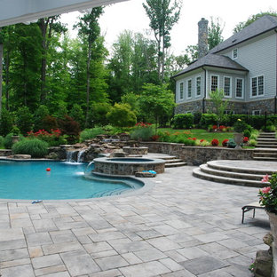 Ejemplo de piscina con fuente natural, ecléctica, de tamaño medio, a medida, en patio lateral, con adoquines de hormigón