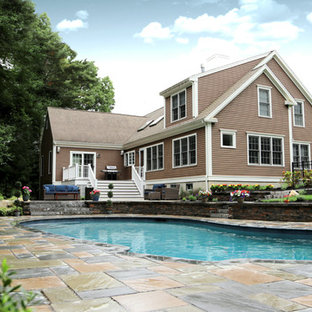 Example of a large classic backyard stone and kidney-shaped lap pool design in Boston