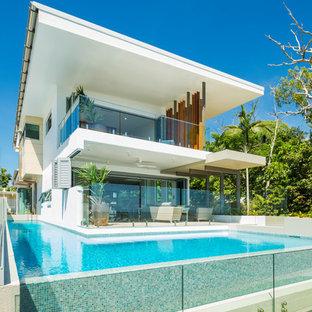 Modelo de piscina alargada, actual, de tamaño medio, en forma de L, en patio delantero