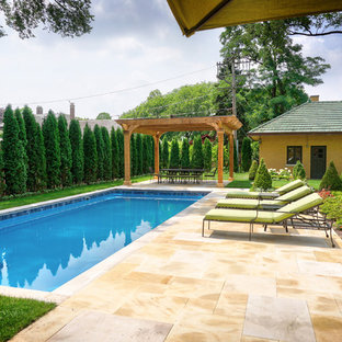 Design ideas for a mid-sized traditional backyard rectangular pool with a pool house and natural stone pavers.