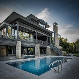 Modelo de piscinas y jacuzzis infinitos, actuales, de tamaño medio, rectangulares, en patio trasero, con adoquines de piedra natural