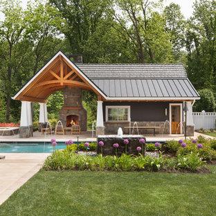 Ejemplo de casa de la piscina y piscina alargada, tradicional, grande, rectangular, en patio trasero, con adoquines de hormigón