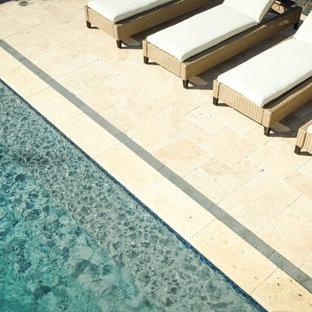 Ejemplo de piscina clásica renovada, grande, rectangular, en patio trasero, con adoquines de piedra natural