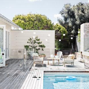 Immagine di una piscina costiera rettangolare di medie dimensioni e dietro casa con pedane