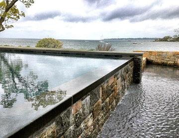 OCEAN: vanishing edge infinity swimming pool + natural stone surround